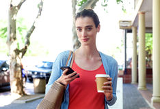 Woman walking on sidewalk holding cellphone and coffee Stock Photo