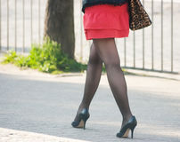 Woman walking on the sidewalk royalty free stock image