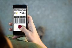 Woman walking smartphone boarding pass. Top view of woman walking in the street using her mobile phone with boarding pass. All screen graphics are made up royalty free stock images