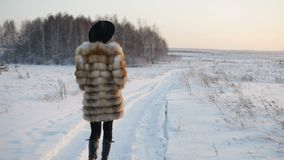 Woman is walking on the snow field stock video footage