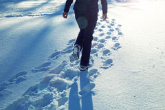 Woman walking in snow at sunny day Stock Photos