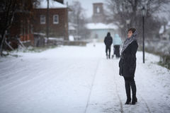 Woman walking in  snowy town Royalty Free Stock Image