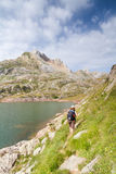 Woman walking in the spanish pyrenees by Estanes lake during sun Stock Images
