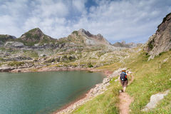 Woman walking in the spanish pyrenees by Estanes lake during sun Royalty Free Stock Photography