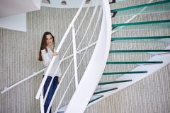 Woman walking on spiral stairs Stock Images