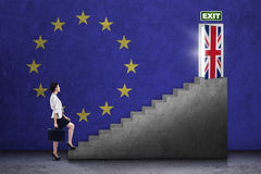 Woman walking on stairs toward brexit door Stock Photography