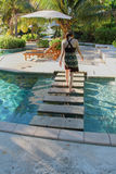 Woman walking on steps across pool Stock Images