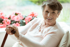 Woman with walking stick smiling. Elder lady sitting on the couch with wooden walking stick and smiling stock photo