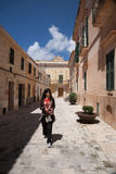 Woman walking in street of Ciutadella city in Minorca. Tourist woman with camera in hands walking in street in old town of Ciutadella city, in Menorca, Balearic Stock Photo