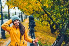 Woman walking on a street full of yellow leaves during Autumn Stock Photos