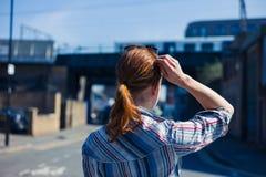 Woman walking in the street near trainline Stock Photos