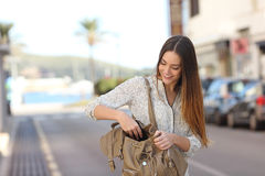 Woman walking on the street and searching in a bag. Casual happy woman walking on the street and searching something in a bag royalty free stock photo