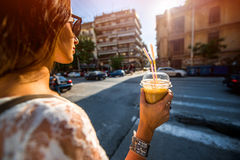 Woman walking on the street with take away coffee Royalty Free Stock Image