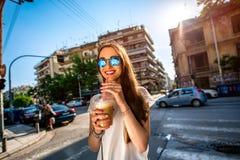 Woman walking on the street with take away coffee Stock Image