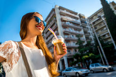 Woman walking on the street with take away coffee Royalty Free Stock Images