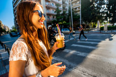 Woman walking on the street with take away coffee Stock Photo