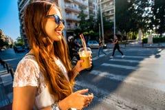 Woman walking on the street with take away coffee Stock Photo