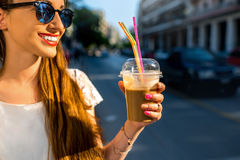 Woman walking on the street with take away coffee. Young woman walking on the street with take away coffee  in the transparent cup in the city Royalty Free Stock Photos