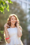 Woman walking on the street and talking by phone Stock Photography