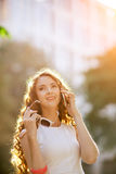 Woman walking on the street and talking by phone Stock Images