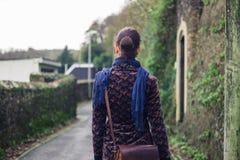 Woman walking in street of village Stock Photos