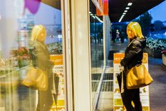 Woman walking in the streets admiring shop windows intent on doing shopping. Woman walking streets admiring shop windows intent doing shopping royalty free stock photography