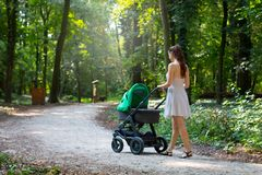 Young woman walking with the pram, baby stroller outdoor in the park. Woman in dress walking with her baby in the stroller/pram outside, natural trail in city stock photo