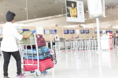 Woman walking suitcase luggage bag on trolley in the airport. Blurred motion selective royalty free stock image
