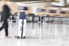 Woman walking suitcase luggage bag on trolley in the airport. Blurred motion selective stock photos