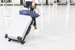Woman walking suitcase luggage bag on trolley in the airport. royalty free stock photography