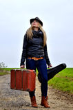 Woman walking with suitcase and violin. Young blond woman with suitcase and violin on the way Royalty Free Stock Image