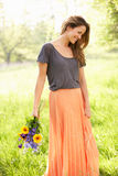Woman Walking In Summer Field Carrying Flowers Stock Photos
