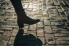 Woman is walking in the sunlight over old street. On an old cobblestone street runs a woman, of whom one sees only the foot; in the background sunlight stock photo