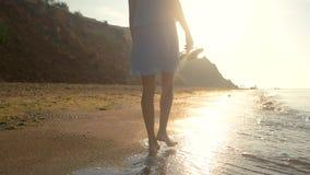 Woman walking on sunny beach. Lady near water stock video