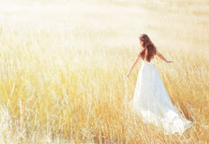 Woman walking in the sunny meadow on summer day
