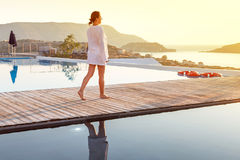 Woman walking at sunrise near swimming pool stock photo