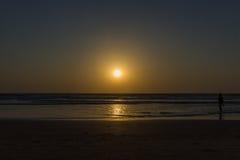 Woman are walking at sunseton Arambol beach, Goa, India Stock Photo