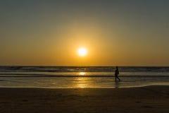 Woman are walking at sunseton Arambol beach, Goa, India Royalty Free Stock Photography