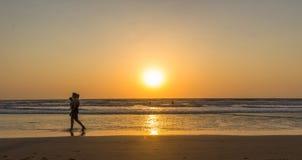 Woman are walking at sunseton Arambol beach, Goa, India.  Stock Photography