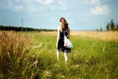 Woman walking through sunshine green and yellow corn field Stock Photos