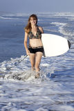 Woman walking with surfboard Stock Photos
