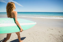 Woman walking with surfboard on beach Stock Photos