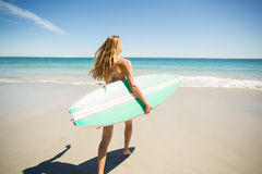 Woman walking with surfboard on beach Royalty Free Stock Images