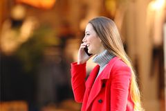 Woman walking and talking on phone in winter in the street. Side view portrait of a woman in red walking and talking on phone in winter in the street royalty free stock images
