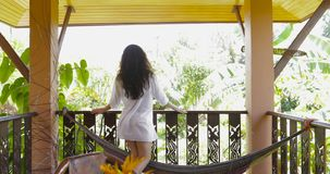 Woman Walking Terrace Looking At Tropical Forest Landscape In Morning Back Rear View Of Attractive Brunette Girl In Man. Shirt Shirt Slow Motion 60 stock video