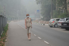 Woman Walking in Thick Smog. YUBILEINY, MOSCOW REGION, RUSSIA - AUGUST 6: Woman is walking down empty street in thick smog with a mask on her face August 6, 2010 Royalty Free Stock Image