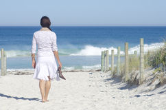 Woman walking to beach at ocean Stock Photos