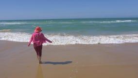 Woman walking to beach, slow motion. 4k stock footage