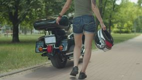 Woman walking to motorcycle with helmet in hand. Midsection of woman motorcycle rider in stylish clothes walking with helmet in hand to parked motorbike outdoors stock video
