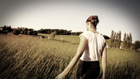Woman walking touching long grass in field in summer - sepia style grading stock footage